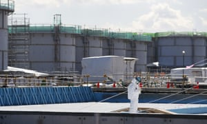 A worker stands in front of storage tanks for radioactive water at the Fukushima Daiichi nuclear power plant