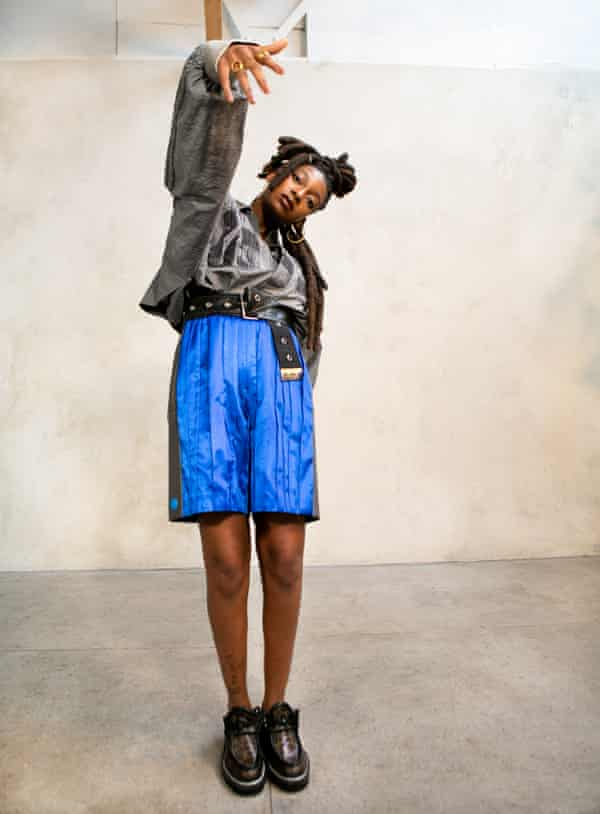 Little Simz standing with one arm up  and fingers down rapper-style, wearing big shiny blue shorts, silver grey top and chunky shoes