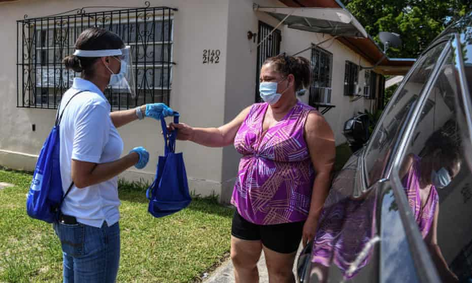 """Catherimarty Burgos, a member of Miami-Dade County """"surge teams"""", distributes bags with masks, sanitizers, and gloves in Miami."""