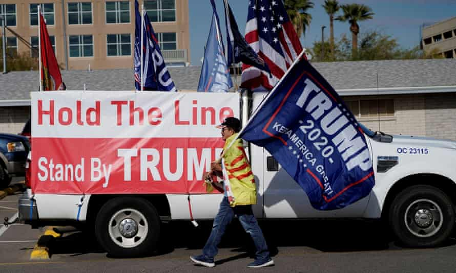A protester caries a Trump 2020 flag in Phoenix, Arizona on 14 December 2020.
