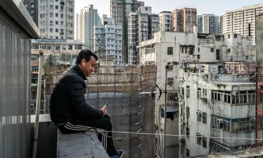 A man speaks on a phone on a rooftop of a residential building in a locked-down part of the Jordon district on January 24, 2021 in Hong Kong, China