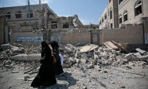 Yemenis walk past rubble after deadly Saudi-led airstrikes in and near the presidential compound, in Sanaa, Yemen, Monday, May. 7, 2018.