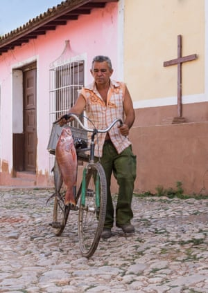 A man in Trinidad, Cuba, returning with his fishing haul, which hangs from the handlebars of his old, green bicycle.