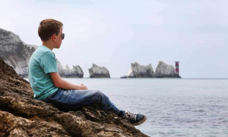 A boy on a rock enjoying the view at The Needles on the Isle of Wight