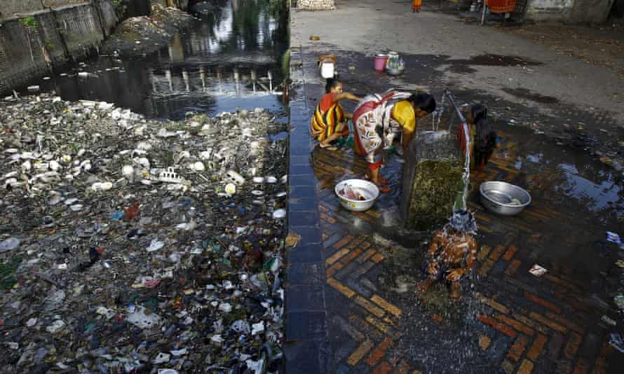 A boy takes a bath under a tap near a polluted water channel in Kolkata
