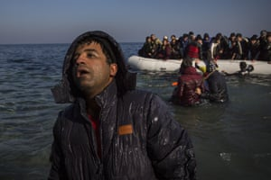 An exhausted man disembarks from a dinghy on a beach next to the town of Mytilene