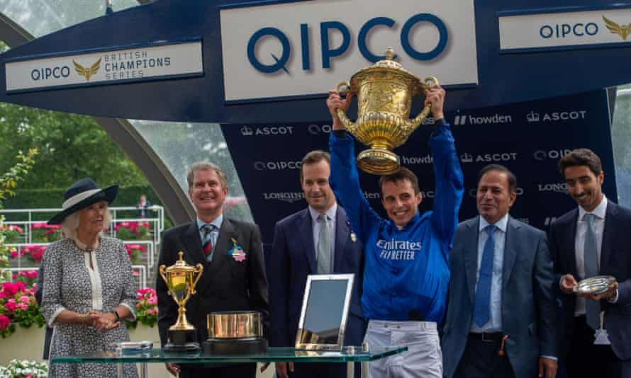 William Buick holds the King George Trophy after victory with Adayar