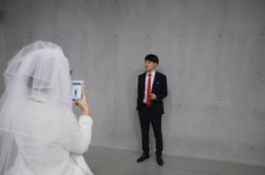 A bride takes photographs of her groom before a mass wedding ceremony of the Unification Church in Gapyeong.