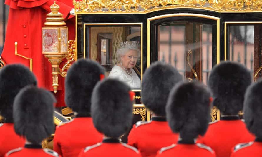 Queen Elizabeth II passes soldiers in a golden carriage