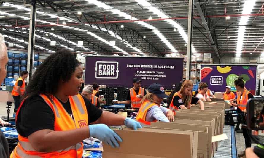 Lizzo packs food into boxes, with volunteers, at a warehouse in Yarraville, Australia, on Jan.8, 2020.