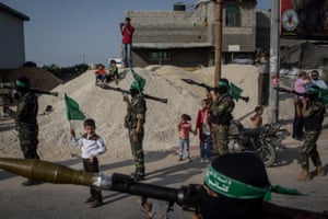 A young boy holds a Hamas flag next to Palestinian militants in the district of Bani Suheila.