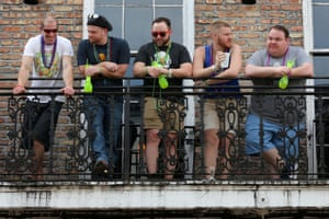 Tourists gather on a Bourbon St. balcony in the French Quarter of New Orleans, Louisiana, US