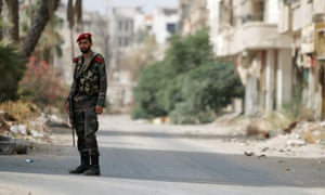 A Syrian army soldier stands at the entrance of the besieged Damascus suburb of Darayya, before the evacuation of residents and insurgents started on Friday.