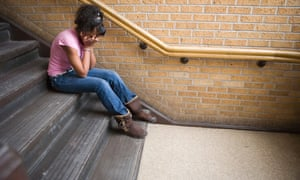 Teenage girl crying on staircase at school