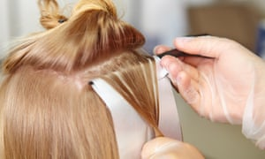 A hairdresser's hands applying colour to someone's hair