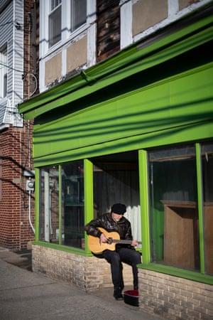 Richard Thompson, playing guitar sitting in urban shopfront.