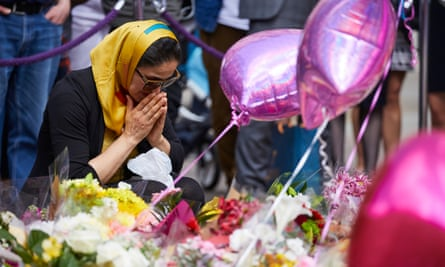 woman with flowers in Manchester to remember those killed in the Manchester Arena attack