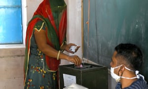 A woman casts her vote at a polling station during Panchayati Raj elections, amid the ongoing coronavirus pandemic, at Jhala ki Chauki village near Beawar, India.
