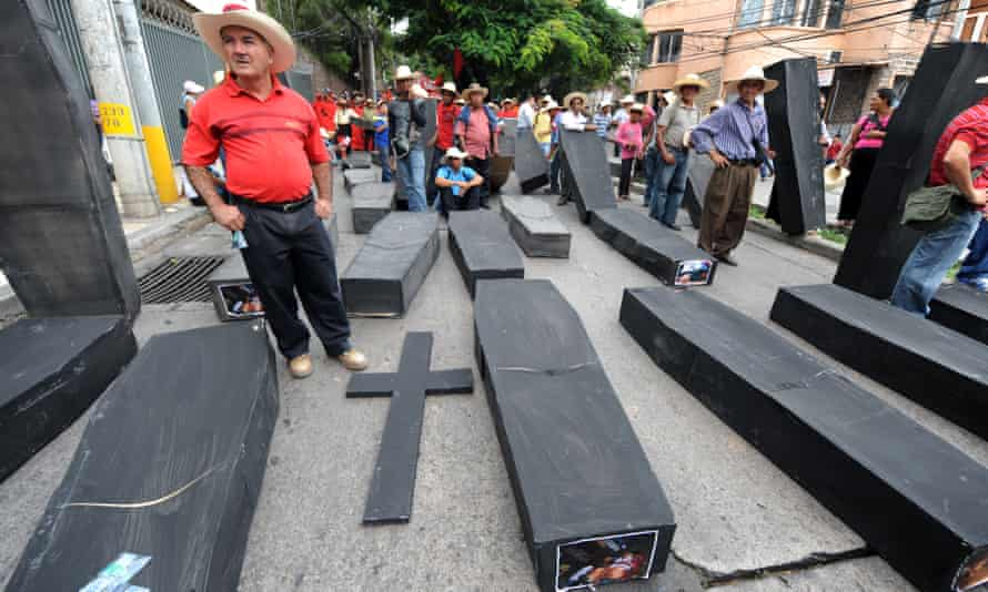 Members of the Peasant Unified Movement (Muca) of Bajo Aguán carry mock coffins bearing pictures of farmers killed in land conflict clashes, in Tegucigalpa, September 2012