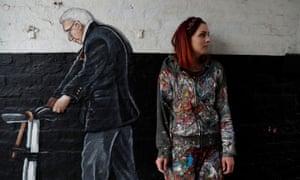 The artist Rachel List strands next to her Pontefract mural of Captain Tom Moore