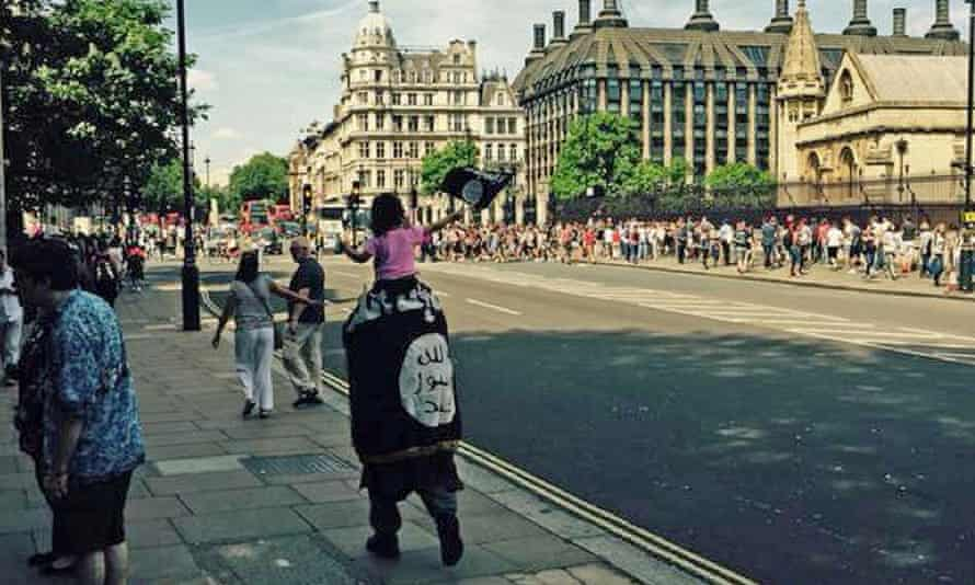 The man wrapped in the Isis flag with a child on his shoulders, also waving the flag, near parliament.