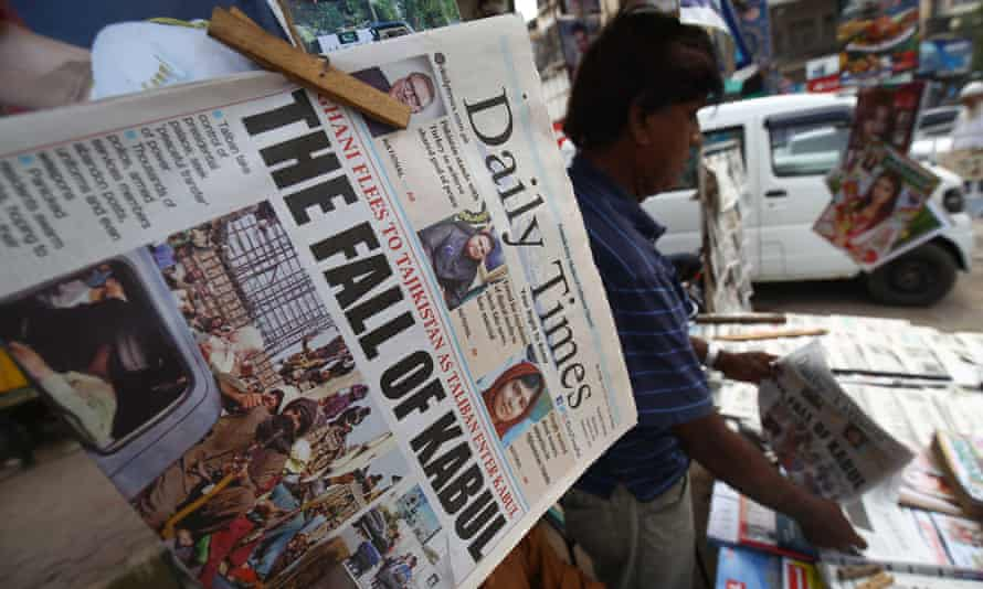 People read front page news of Taliban taking over Kabul, at a newspaper stall in Karachi, Pakistan.