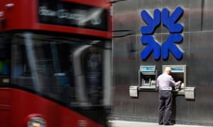 A man collects cash from an RBS ATM bank as a  London bus passes