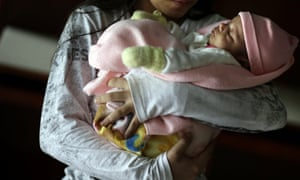 A 13-year-old girl holds her baby at a shelter in Paraguay.
