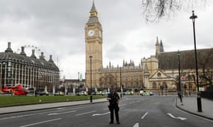 A armed police officer stands guard outside the Houses of Parliament.
