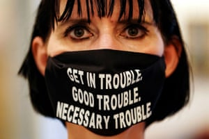 A woman wears a face mask with a quote from the late congressman John Lewis in Atlanta, US