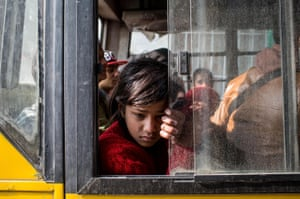 A young girl sits on a bus