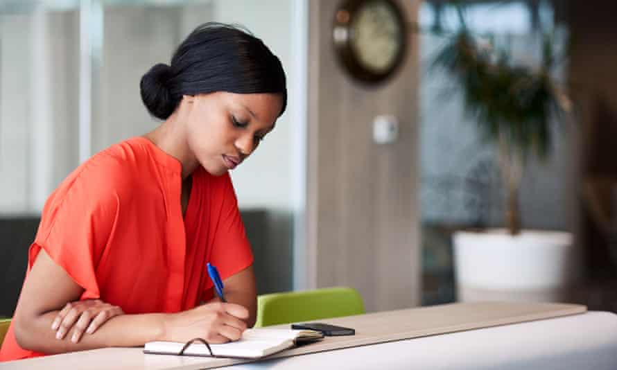 woman sitting down writing in notebook with pen