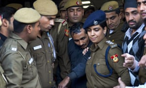 Uber driver Shiv Kumar Yadav, centre, is flanked by police after an earlier court hearing in Delhi, India.