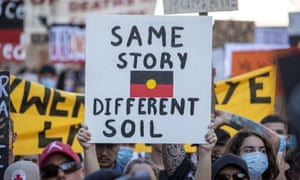 A protester holds a placard depicting the Australian Aboriginal Flag.