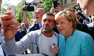 A migrant takes a selfie with Angela Merkel