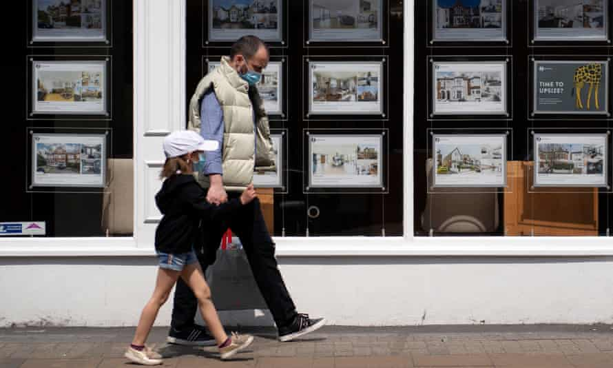A man and child walk past an estate agency in London