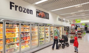 Woman pushing a pram and son shopping in a supermarket frozen food aisleCP3WBF Woman pushing a pram and son shopping in a supermarket frozen food aisle