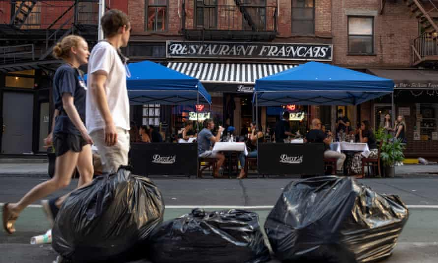 New York Trash bags are see across the street from customers eating outside at Raoul'