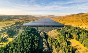 An aerial view of Scar House reservoir, with trees in the foreground, golden grassland on either side and a blue sky with light cloud streaks