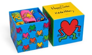 A brightly coloured box and lid, side by side, with several pairs of socks folded inside