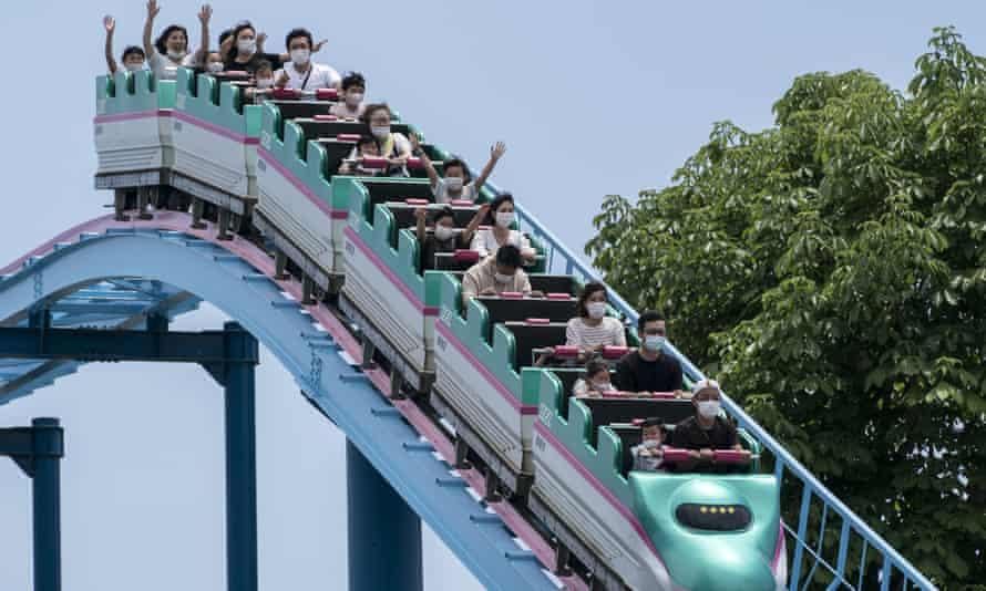 Visitors wearing face masks ride a roller coaster at the Tochinoki Family Land amusement park on May 17, 2020 in Utsunomiya, Tochigi, Japan