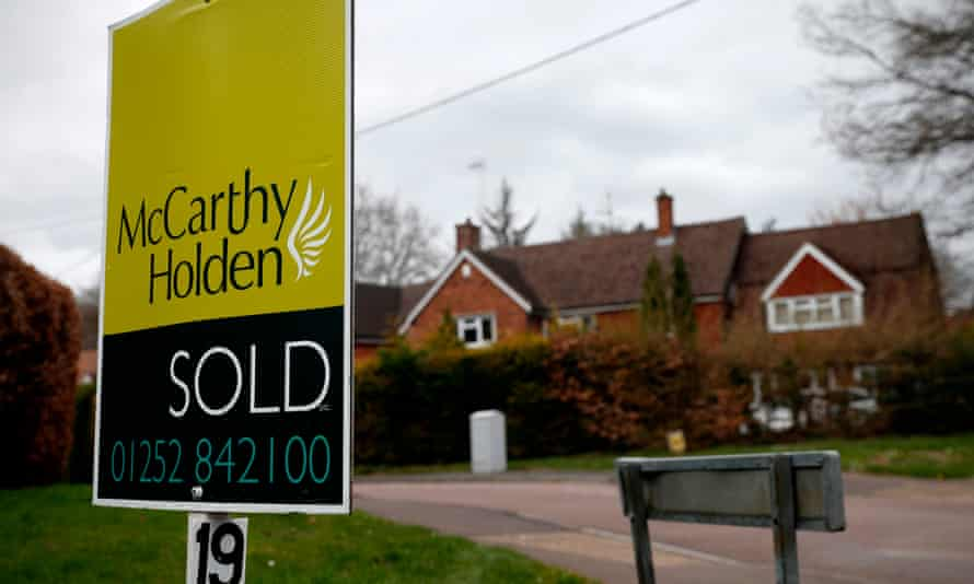 Estate agent sign reading 'sold' outside large house