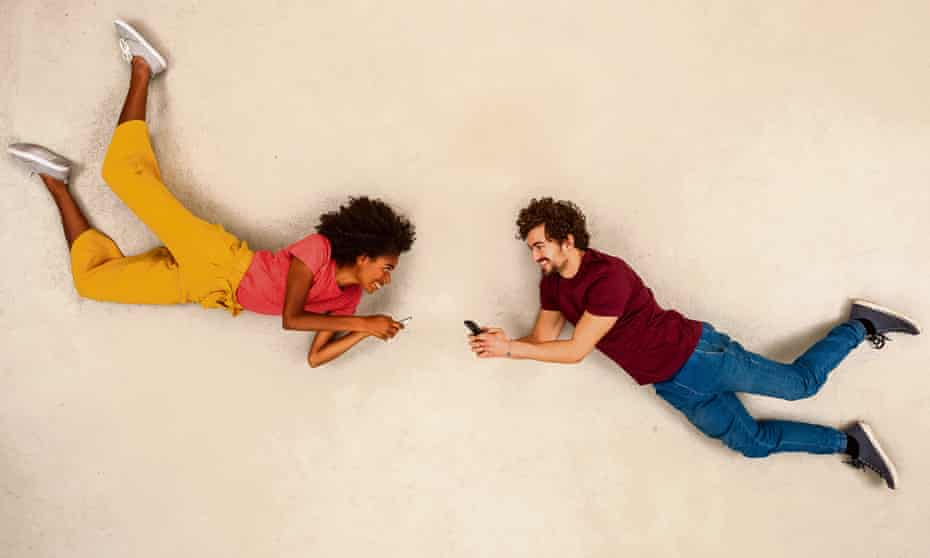 Happy couple texting on their smart phones