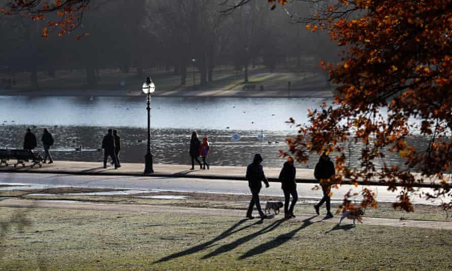 Early morning walkers cast long shadows in Hyde Park in London