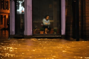 <strong>Dumfries, UK</strong><br>A woman sits inside a Chinese Restaurant watching floodwater race by the window after heavy rainfall brought by Storm Frank