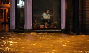 A woman watches floodwaters race past the window of a Chinese restaurant in Dumfries, southern Scotland