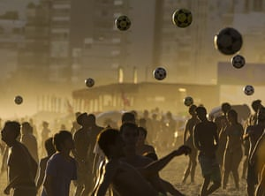 People kick footballs in the air at Ipanema beach in Rio de Janeiro, Brazil