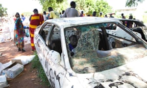 A boy plays in a vandalised car as women wait for food aid in Bentiu town, capital of South Sudan's Unity state