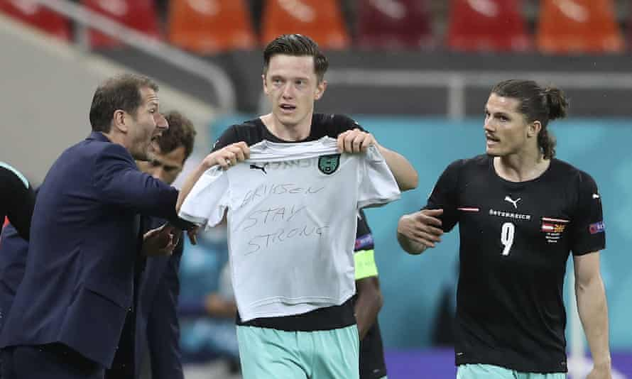 Austria's Michael Gregoritsch holds up a jersey which reads 'Eriksen stay strong' after scoring