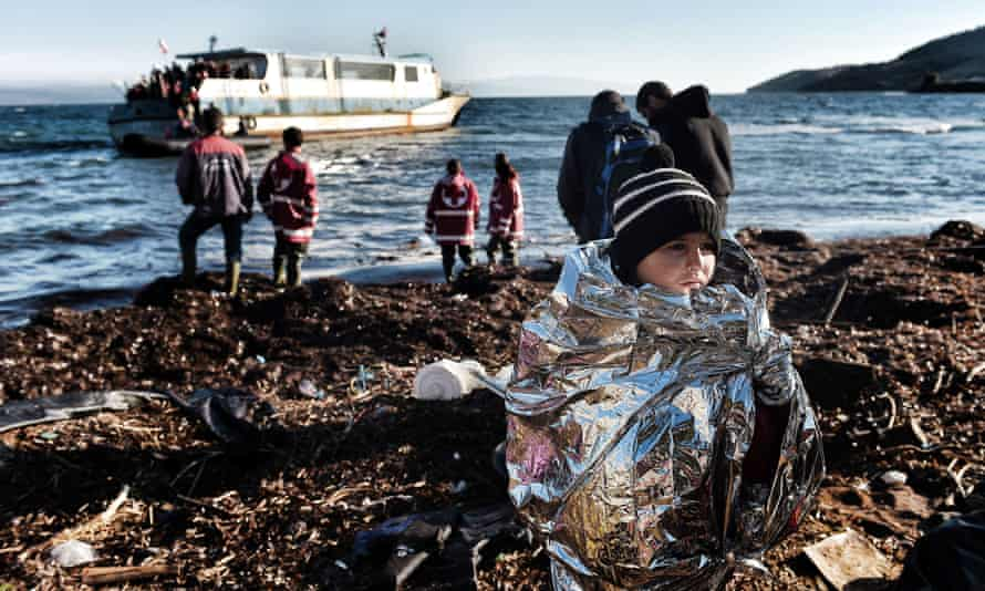 A boy wearing an emergency blanket to warm himself arrives with other refugees on the Greek island of Lesbos.